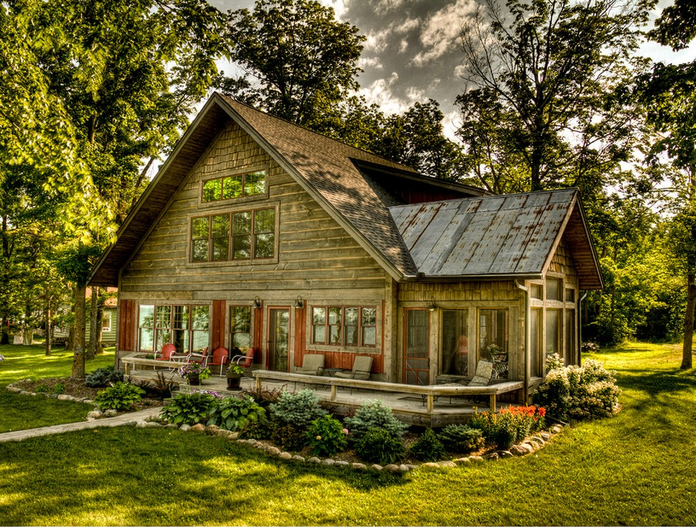 Rustic Cottage With Red Trim Windows And Dark Wood Siding