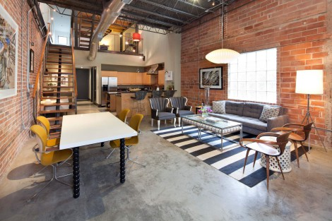 concrete flooring with george nelson light and exposed brick wall