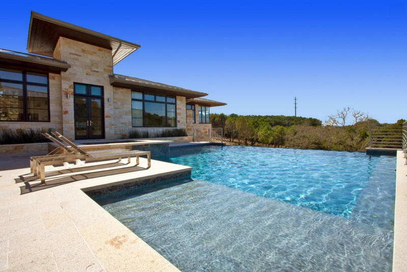 texas stone exterior with poolside chairs