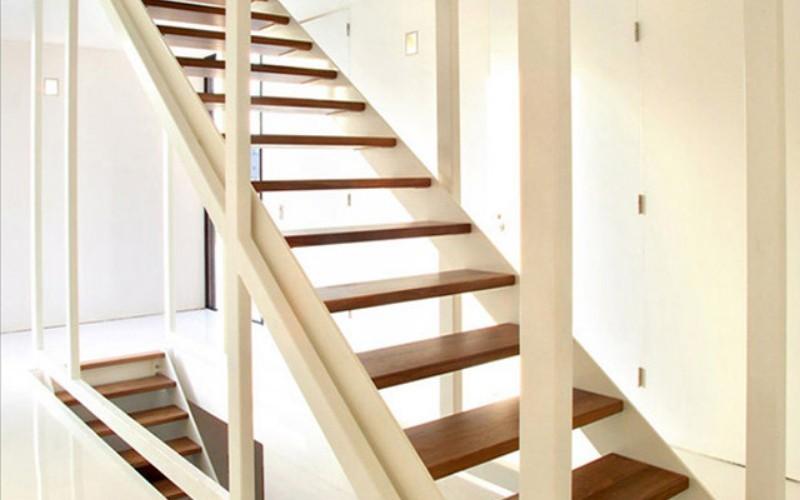 Дизайн подвесной лестницы из темного дерева и белым корпусом