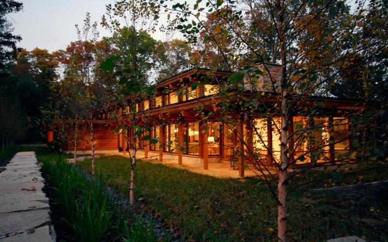 Современный деревянный дом на берегу реки в лесистой местности