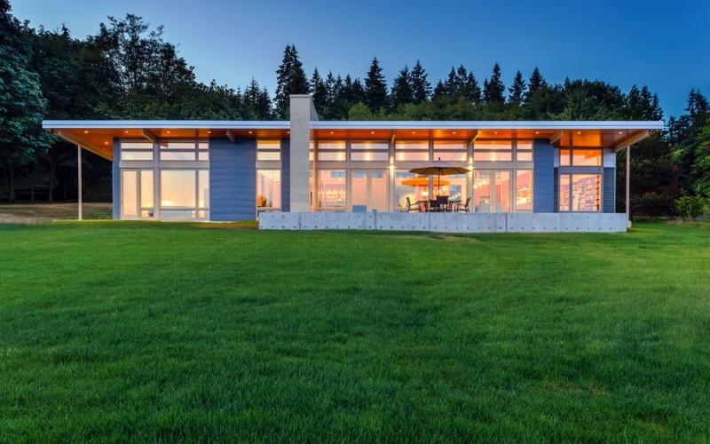 Современный одноэтажный дом на пологом склоне открывает красивый вид на залив