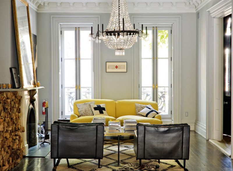 light living room with chandelier and accent woodworking, including yellow couch