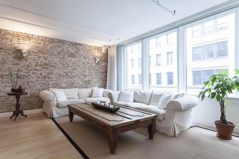 living room with brick wall and white sofa
